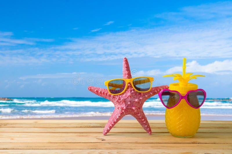 Concept de vacances d'?t? avec le jus mignon d'?toiles de mer et d'ananas avec des lunettes de soleil au-dessus de fond de plage  photo stock