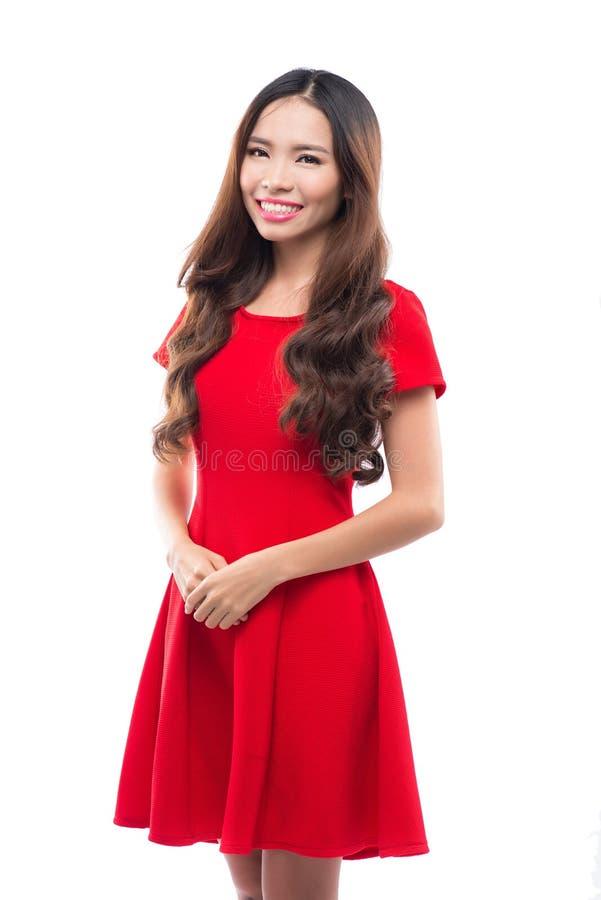 Concept de vacances, de célébration et de personnes - femme de sourire dans la robe rouge sur le fond blanc images stock