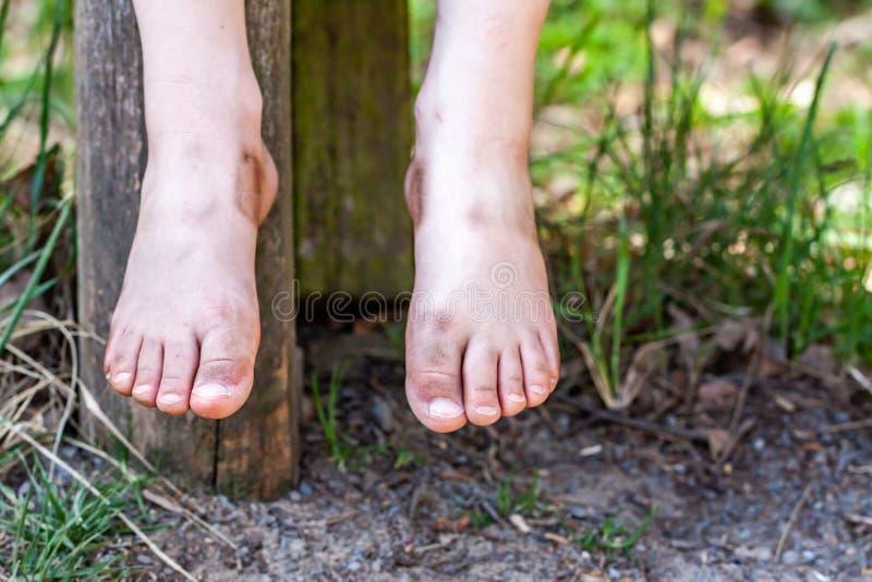 Concept de vacances des pieds sales d'enfant accrochant au-dessus du vert photo libre de droits