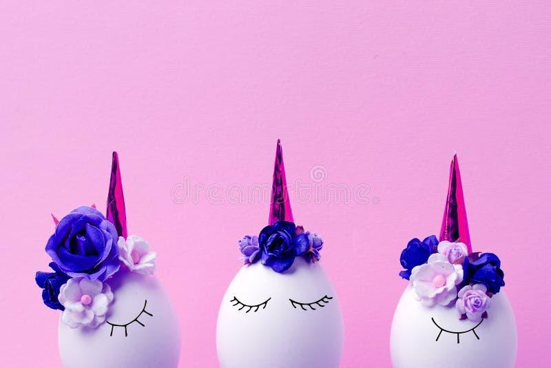 Concept de vacances de Pâques avec les oeufs faits main mignons, ensemble d'oeufs somnolents mignons de licornes de kawaii, fond  photo stock
