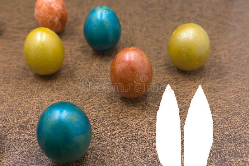 Concept de vacances de Pâques avec les oeufs, le lapin, les poussins et les chapeaux faits main mignons de partie images libres de droits