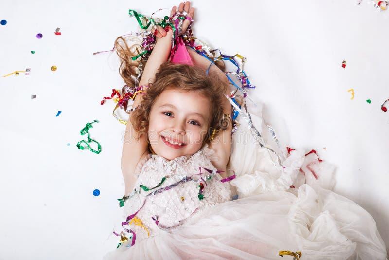Concept de vacances Peu fille drôle se situant dans les confettis multicolores sur la fête d'anniversaire photos stock