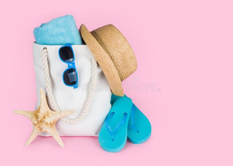 Concept de vacances de plage avec des bascules et sac sur le fond rose images stock