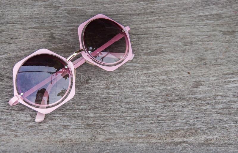 Concept de vacances de plage - fermez-vous vers le haut des lunettes de soleil mignonnes roses de femmes sur la table photographie stock libre de droits