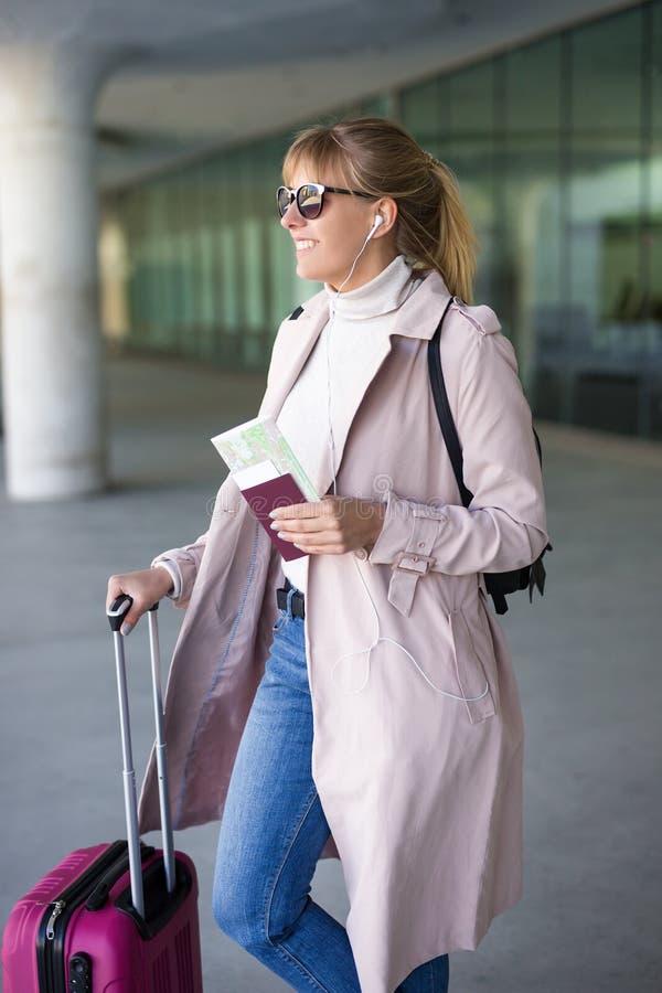 Concept de vacances, de tourisme et de voyage - jeune touriste féminin avec l'embarquement de attente de valise et de passeport d photos libres de droits