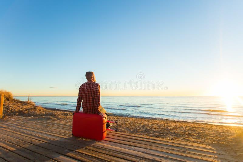 Concept de vacances de vacances, de voyage et d'été - un homme s'asseyant sur la valise rouge et observant le coucher du soleil photo stock