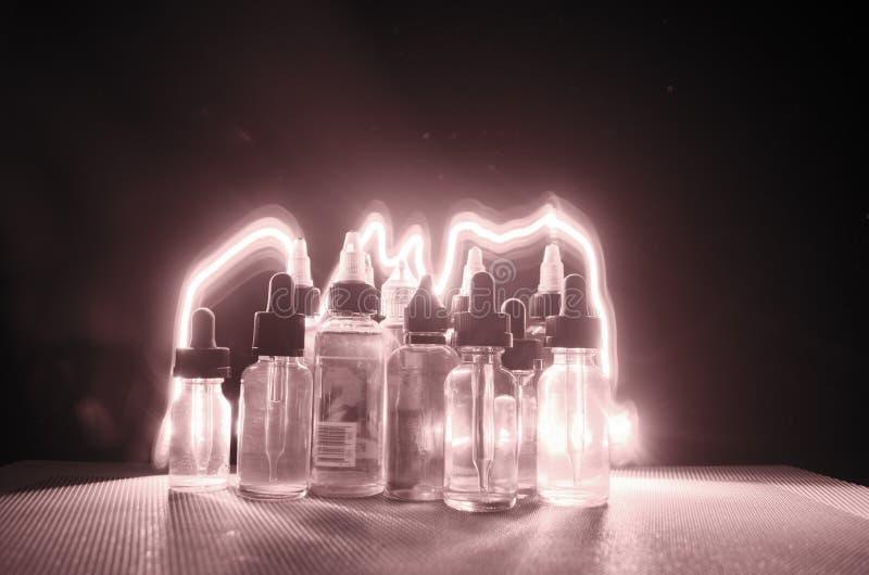 Concept de Vape Nuages de fumée et bouteilles liquides de vape sur le fond foncé Effets de la lumière photographie stock