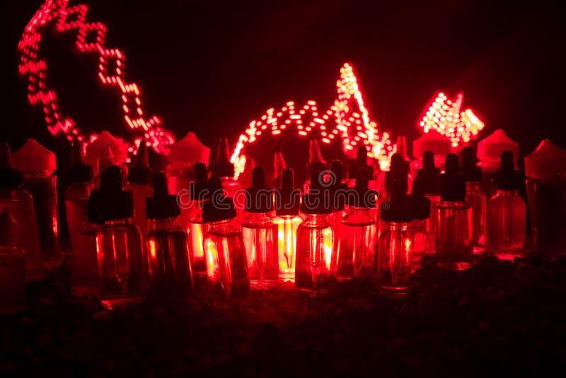 Concept de Vape Nuages de fumée et bouteilles liquides de vape sur le fond foncé Effets de la lumière Utile comme fond ou cigaret photographie stock libre de droits