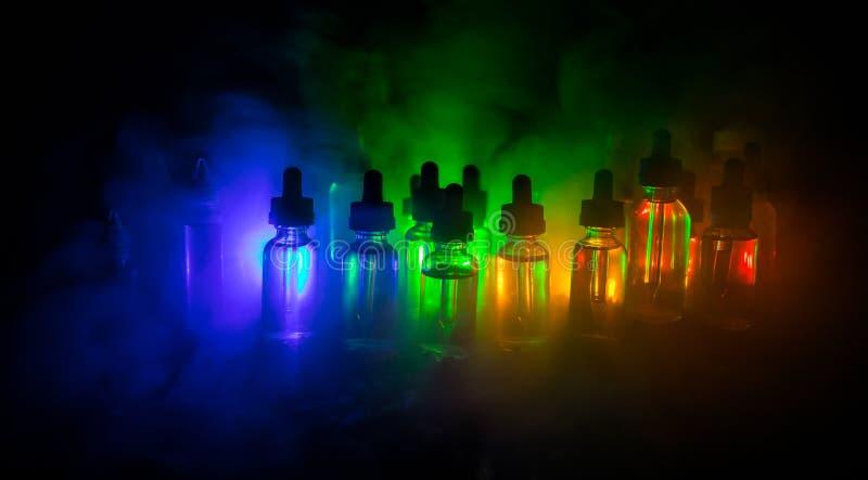 Concept de Vape Nuages de fumée et bouteilles liquides de vape sur le fond foncé Effets de la lumière Utile comme fond ou cigaret image stock