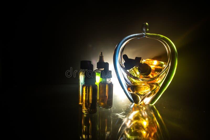 Concept de Vape Nuages de fum?e et bouteilles liquides de vape sur le fond fonc? Effets de la lumi?re Utile comme fond ou cigaret image stock