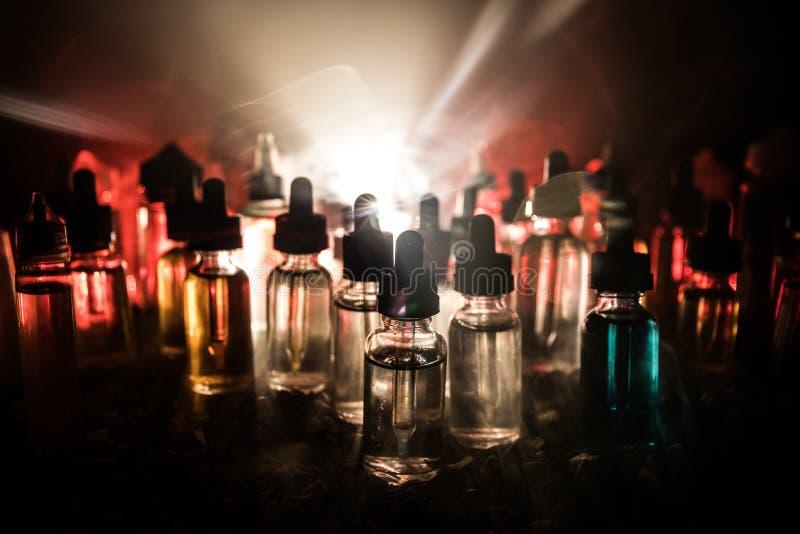 Concept de Vape Nuages de fum?e et bouteilles liquides de vape sur le fond fonc? Effets de la lumi?re Utile comme fond ou cigaret photographie stock