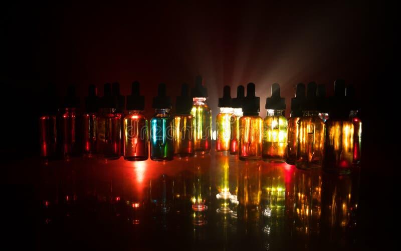 Concept de Vape Nuages de fum?e et bouteilles liquides de vape sur le fond fonc? Effets de la lumi?re Utile comme fond ou cigaret photo libre de droits