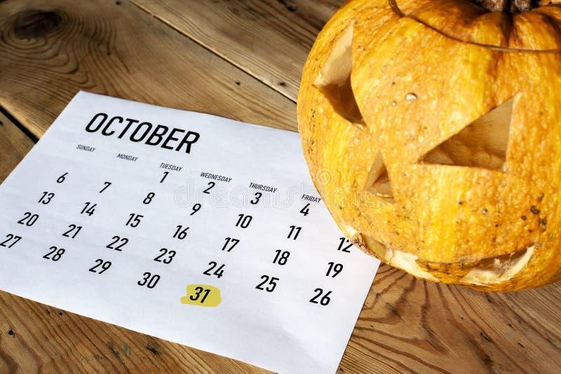 Concept de Veille de la toussaint Le calendrier d'octobre avec le jour de Halloween a accentué et potiron - le feu follet photographie stock