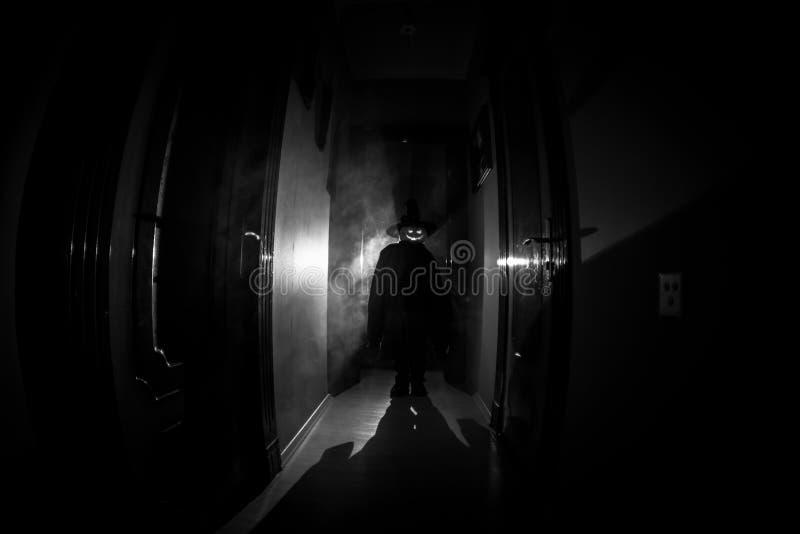 Concept de Veille de la toussaint Silhouette rampante dans le couloir sombre avec la tête de potiron Lumière modifiée la tonalité photos libres de droits