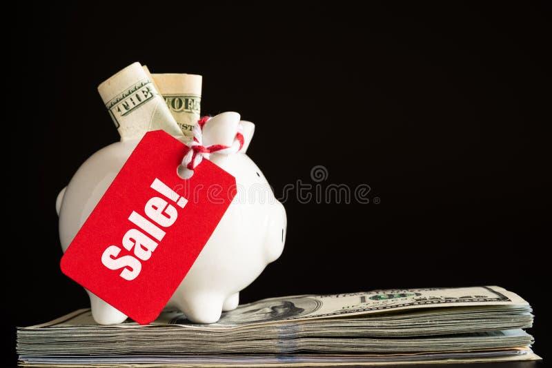 Concept de vente d'achats avec l'étiquette rouge de vente de billet accrochant avec la tirelire photo stock