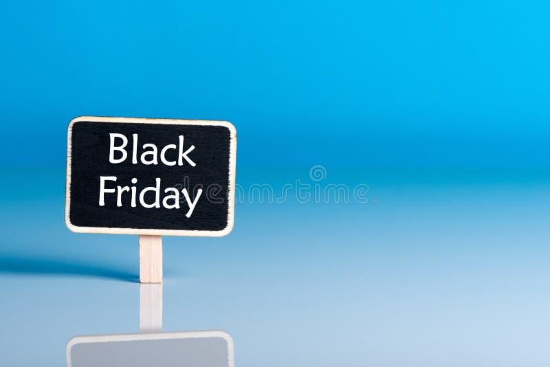 Concept de vente d'achats de Black Friday avec peu d'étiquette en bois Fin d'étiquette de vente sur le fond bleu Temps d'achats J images stock