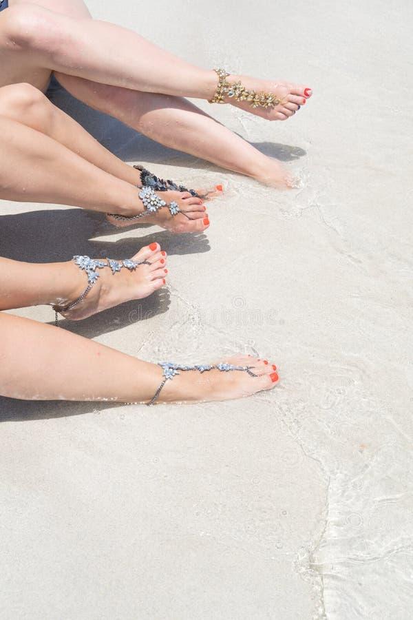 Concept de vibe de vacances de poussin Jambes de femme avec des bijoux de jambe sur la plage blanche tropicale de sable photographie stock libre de droits