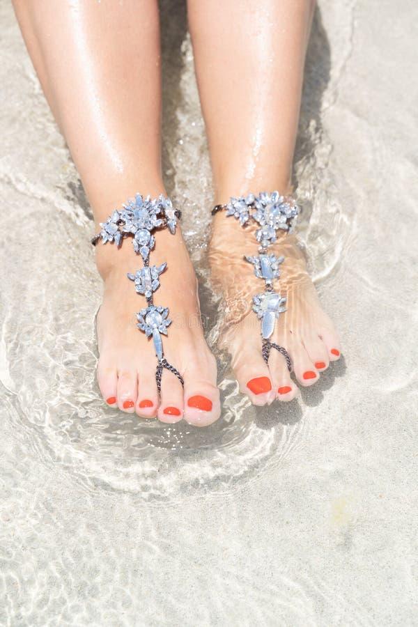 Concept de vibe de vacances de poussin Jambes de femme avec des bijoux de jambe sur la plage blanche tropicale de sable images stock