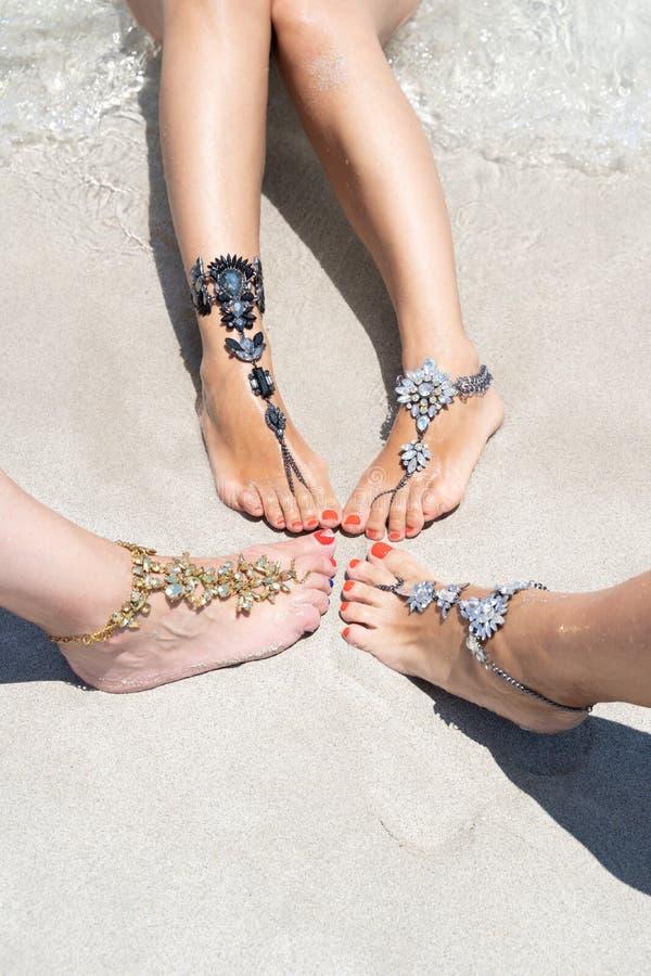 Concept de vibe de vacances de poussin Jambes de femme avec des bijoux de jambe sur la plage blanche tropicale de sable photo libre de droits