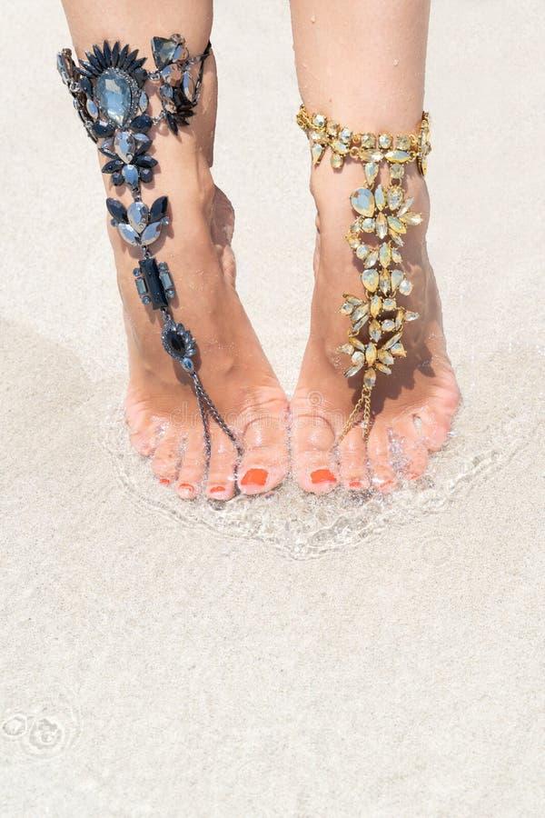 Concept de vibe de vacances de poussin Jambes de femme avec des bijoux de jambe sur la plage blanche tropicale de sable photos stock