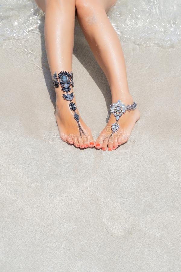 Concept de vibe de vacances de poussin Jambes de femme avec des bijoux de jambe sur la plage blanche tropicale de sable photos libres de droits