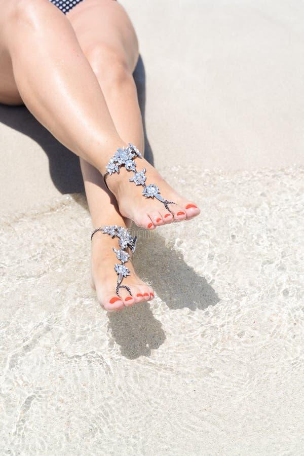 Concept de vibe de vacances de poussin Jambes de femme avec des bijoux de jambe sur la plage blanche tropicale de sable images libres de droits