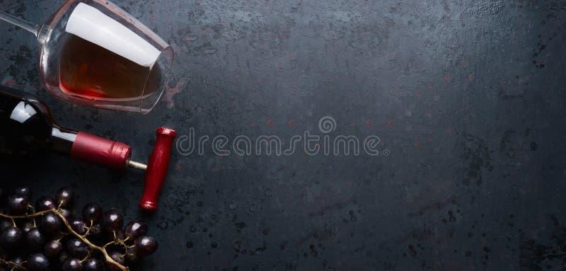 Concept de vin rouge Le verre de vin avec la bouteille et le raisin rouge groupe sur le fond rustique noir, vue supérieure, images libres de droits