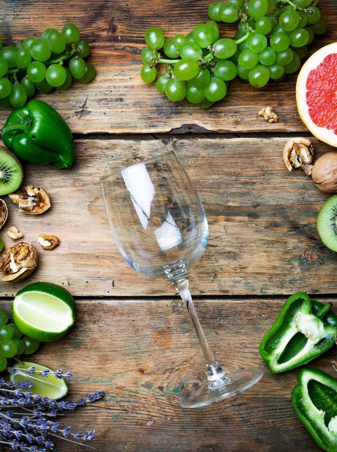 Concept de vin Verre de jeune bio vin blanc avec des raisins verts, le pamplemousse et tout autre fruit sur une vieille table en  photo libre de droits