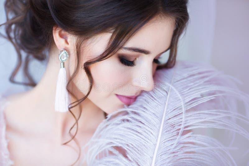 Concept de visage et de soins de la peau de corps Jeune belle femme, portrait en gros plan avec la grande plume blanche près du v photo stock