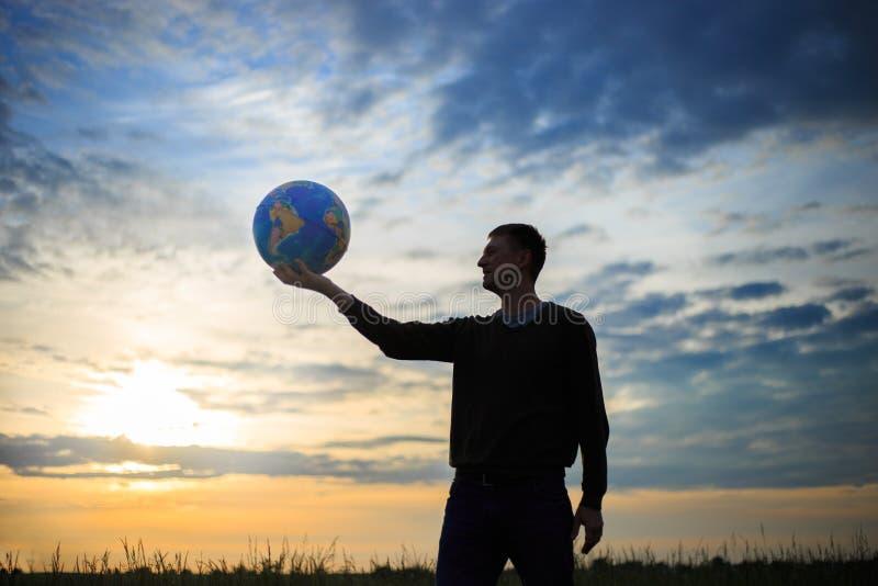 Concept de voyage avec la main de l'homme et la terre ronde avec des points de repère photos stock