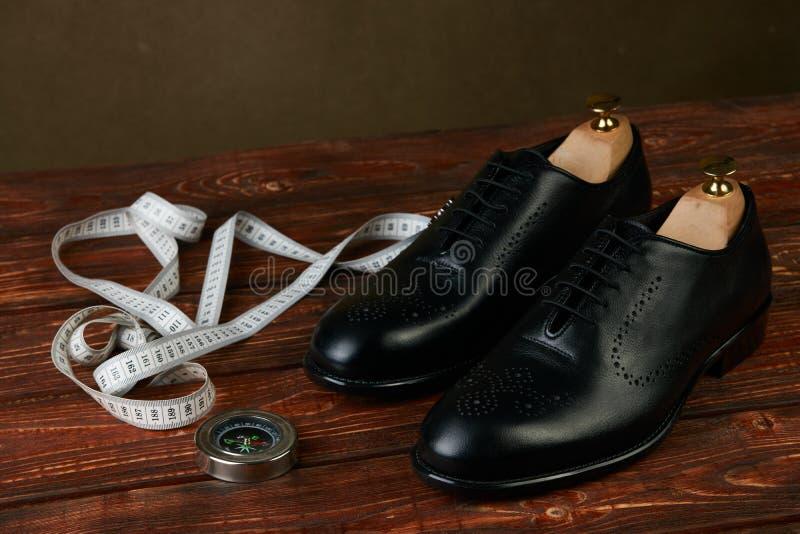 Concept de voyage d'affaires avec des paires des chaussures des hommes de couleur, de la boussole et de la bande de mesure photos stock