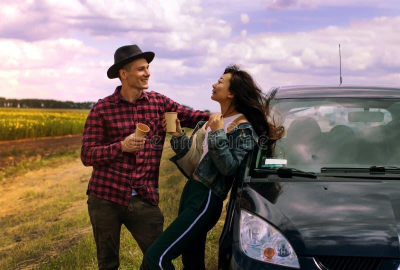 Concept de voyage, d'amour, de date et de personnes - couple heureux étreignant la détente avec du café sur la route photos libres de droits