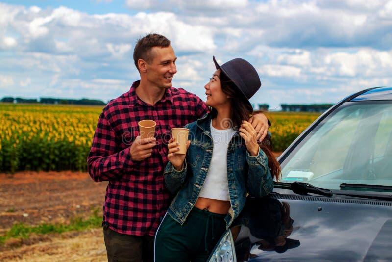 Concept de voyage, d'amour, de date et de personnes - couple heureux étreignant la détente sur la route photo libre de droits