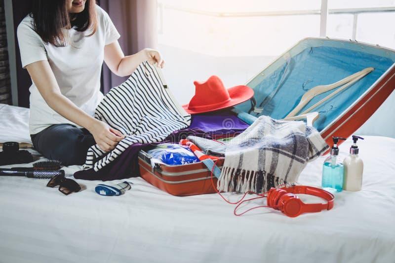 Concept de voyage et de vacances, jeune femme de bonheur emballant beaucoup image stock