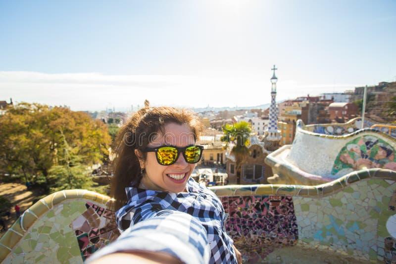 Concept de voyage et de vacances - jeune femme heureuse faisant le portrait de selfie avec le smartphone en parc Guell, Barcelone images libres de droits
