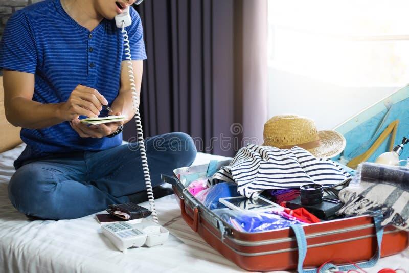 Concept de voyage et de vacances, jeune homme de bonheur emballant beaucoup o photographie stock