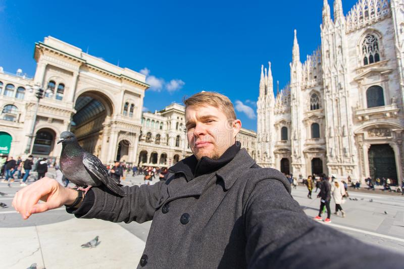 Concept de voyage, de vacances et de vacances d'hiver - photo heureuse de selfie de prise d'homme avec les pigeons dr?les devant  photo libre de droits
