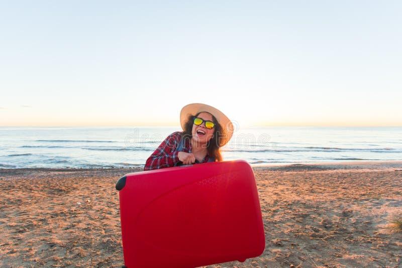 Concept de voyage, de vacances et de vacances - valise drôle de participation de jeune femme sur la plage photographie stock libre de droits