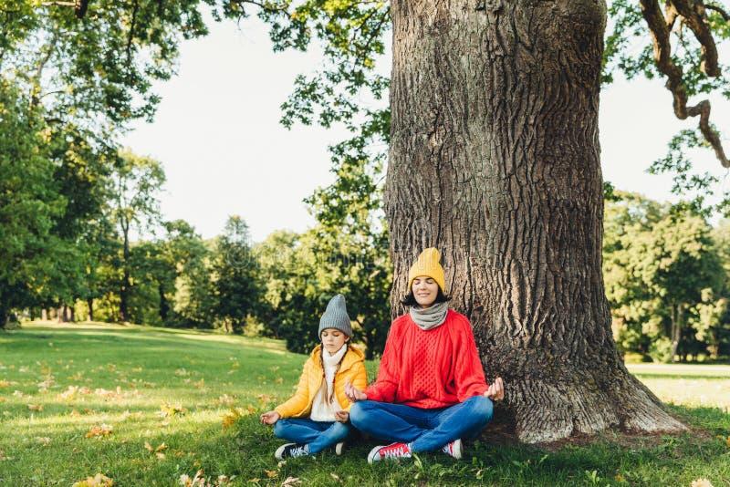 Concept de yoga et de méditation La belle jeune femme dans des vêtements tricotés et le petit enfant maintiennent des yeux fermés photo libre de droits