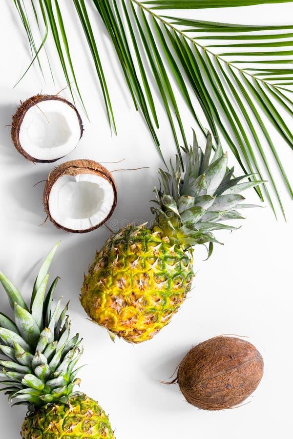 Concept de zomer tropische vruchten Ananas, kokosnoten en palmtak op witte hoogste mening als achtergrond stock afbeelding
