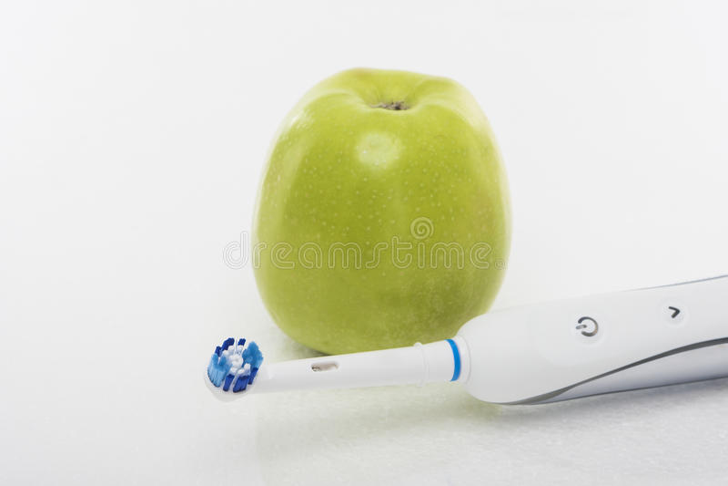 Concept dentaire de Hygien : Pomme verte ainsi que Toothb électrique photographie stock