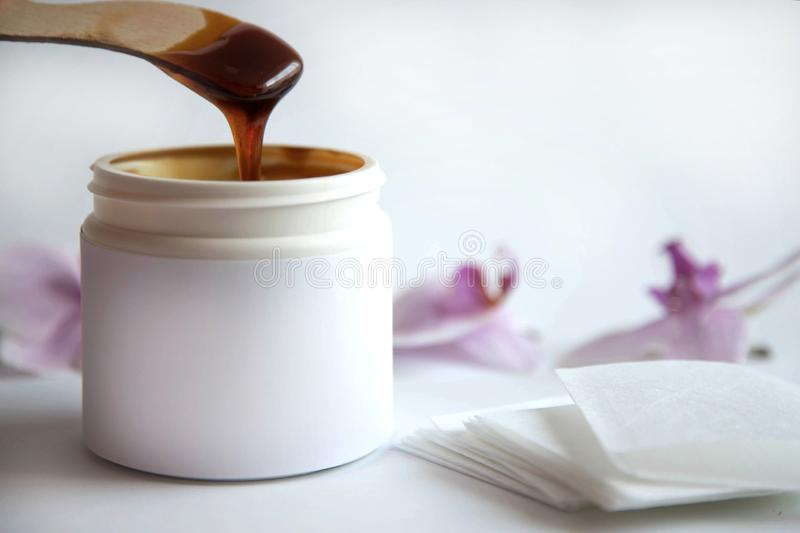 The concept of depilation and beauty is sugar paste or hair removal wax in a white plastic jar with a wooden wax spatula in melted. Paste and stripes for hair stock photography
