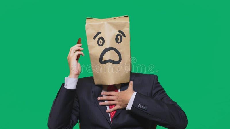 Concept des émotions, gestes un homme avec des sacs en papier sur sa tête, avec une émoticône peinte, crainte Parler à un télépho image libre de droits