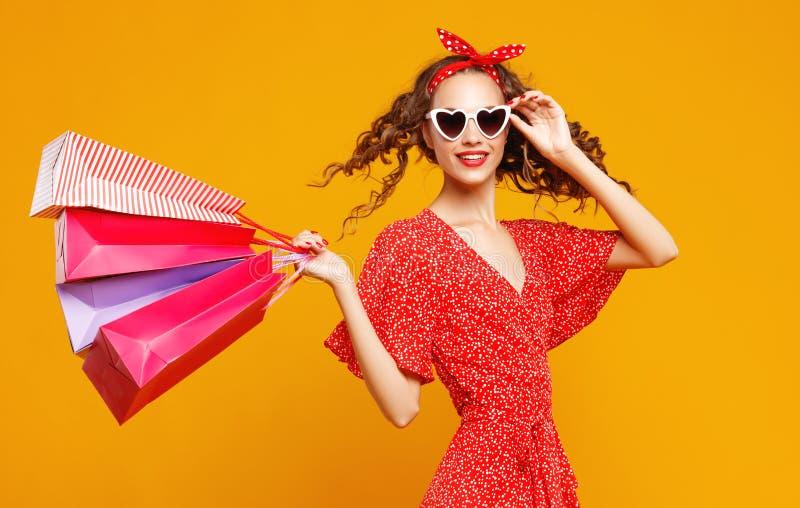 Concept des achats d'achats et ventes de fille heureuse avec des paquets sur le fond jaune images libres de droits