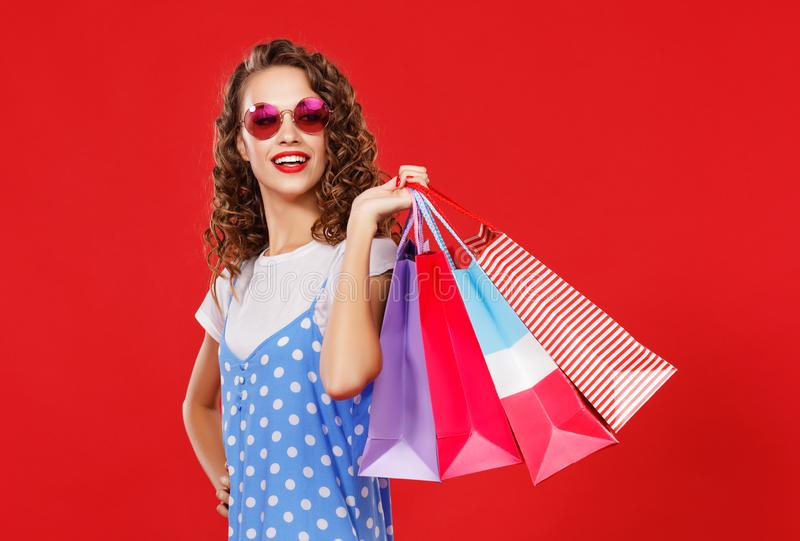 Concept des achats d'achats et ventes de fille heureuse avec des paquets sur le fond rouge photographie stock libre de droits