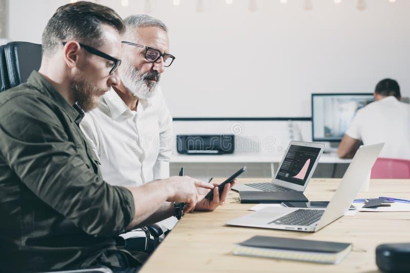 Concept des gens d'affaires faisant un brainstorm Main barbue de pointinh d'homme sur l'écran du téléphone portable photo libre de droits