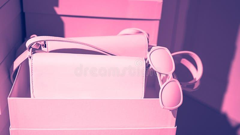 Concept des lunettes de soleil femelles à la mode de sacs d'accessoires sur les boîtes vides et le fond rose photos stock