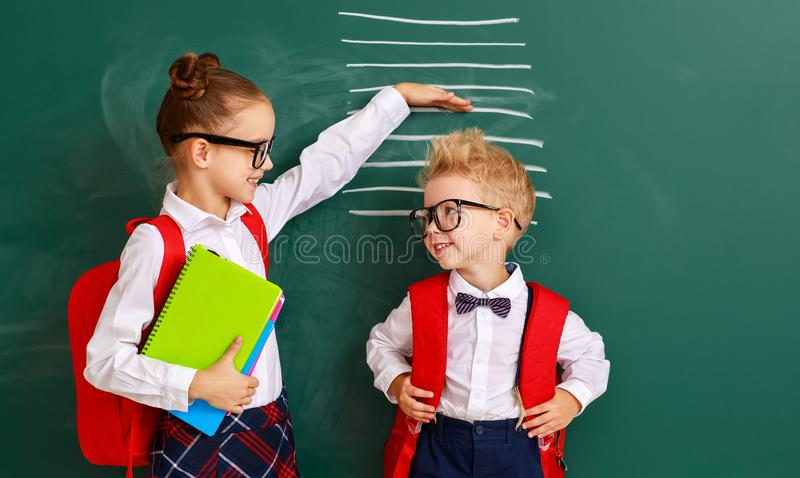 Concept of   development in education. children boy and girl students measure growth about school blackboard stock photography