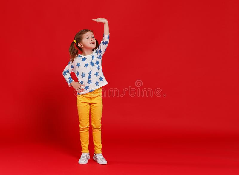 Concept of development and growth,   kid girl measuring height on  red colored background. Concept of development and growth,  kid girl measuring height on a red royalty free stock photo
