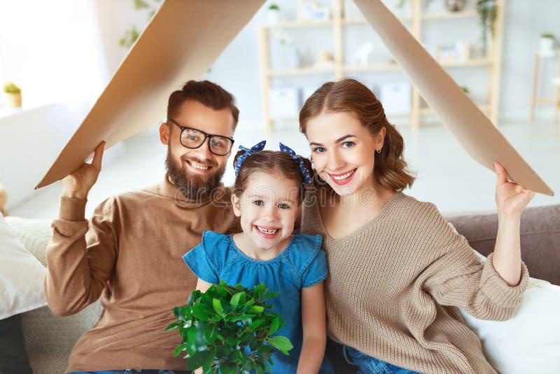 Concept die jonge familie huisvesten Moedervader en kind in nieuw huis met dak thuis royalty-vrije stock fotografie
